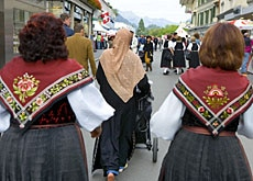 A Muslim woman walks in front of women in traditional Swiss dress