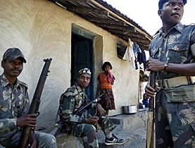 A child watches as armed officers rest outside her hut in the Dantewada district of India's state of Chhattisgarh