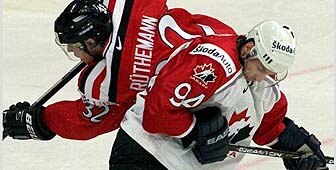 Switzerland's Ivo Rüthemann (l.) battles for the puck with Canada's Ryan Smith