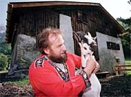 "Heidi's grandfather poses with one of his goats in front of the ""Heidi House"""