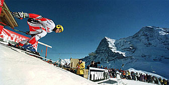 Austria's Hermann Maier throws himself out of the starting gate with the Eiger and Mönch in the background
