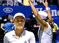Martina Hingis contemplates her defeat while Jennifer Capriati celebrates her victory