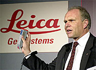 Hans Hess, CEO of Leica Geosystems, shows off one of his company's hand-held distance measuring devices: Leica is expected to report results this week