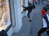 Protesters smash the windows of a branch of UBS bank in Basel