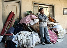 A Sunni boy in Baghdad stands in front of his family's belongings