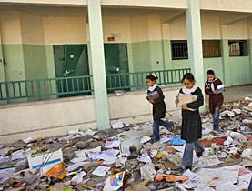 Palestinian schoolgirls walk through the rubble of the Sakhnin School in Beit Lahiya, in the north of the Gaza Strip