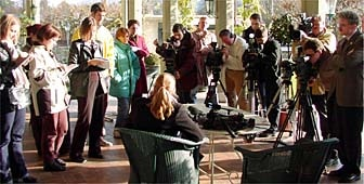 Woman in chair with back to camera talks to journalists with notepads, cameras.
