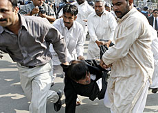 Police carry a lawyer who was rallying in Lahore against President Musharraf's declaration of a state of emergency