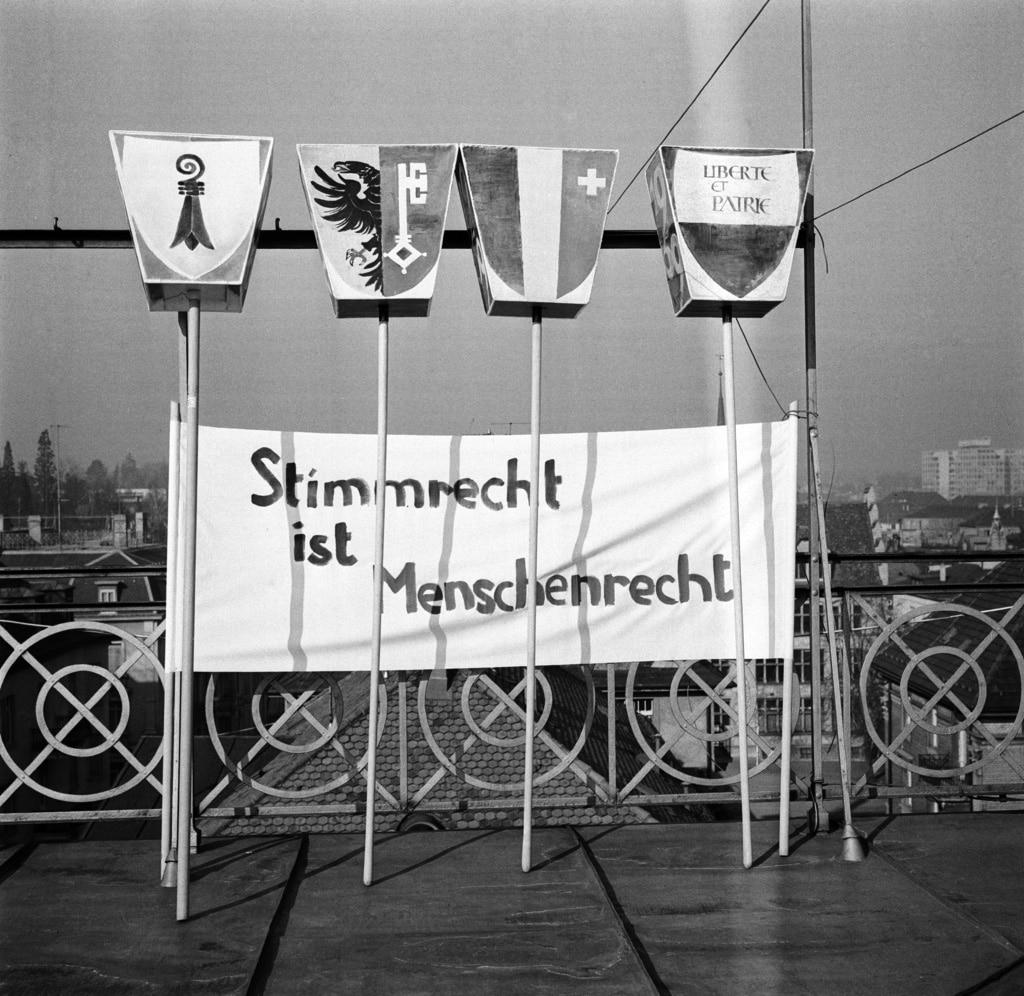 「参政権は人権」 – 1966年、チューリヒの建物の屋上に掲げられた横断幕。州レベルで女性参政権を導入した州のワッペンが立てかけられている