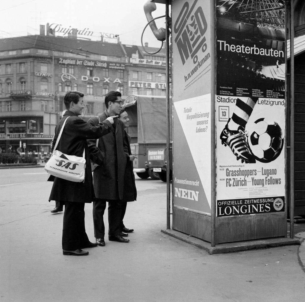 1966年、日本人観光客がチューリヒの電話ボックスに貼られた女性参政権導入反対を訴えるポスターを眺める