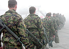 The country's first armed peacekeepers leave for Kosovo in thick fog