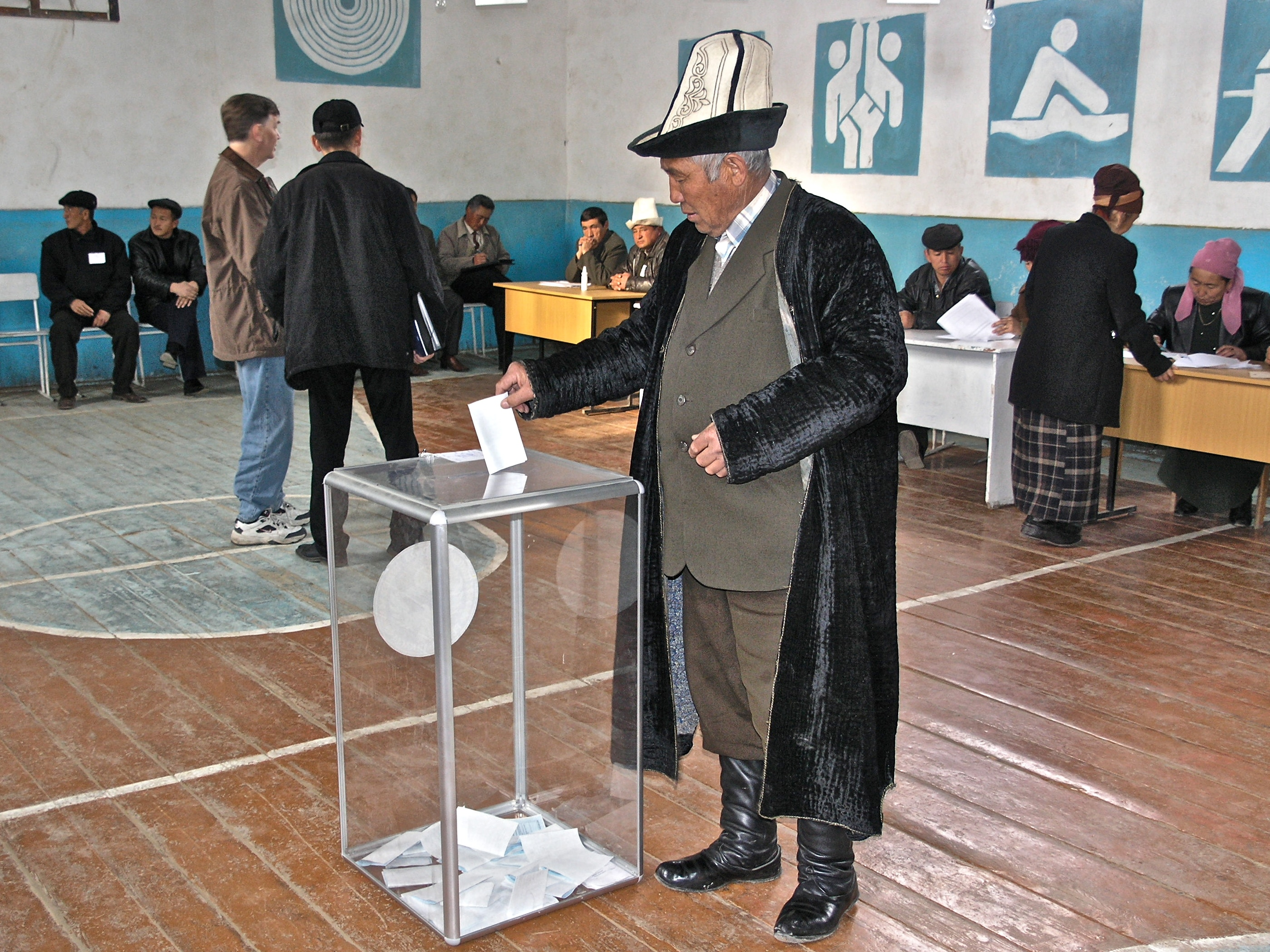Local election observers and polling station workers look on as a man casts his ballot during the 2005 parliamentary elections in Kyrgyzstan.