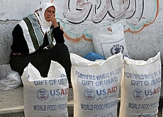 A Palestinian woman sitting next to sacks of flour at a UN aid distribution centre in Gaza City