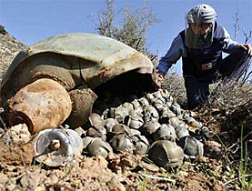 An expert examines a cluster bomb in Lebanon following fighting there in 2006