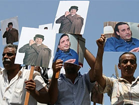 Protesters hold signs of Libyan leader Moammar Gaddafi and his son Hannibal outside the Swiss embassy in Tripoli
