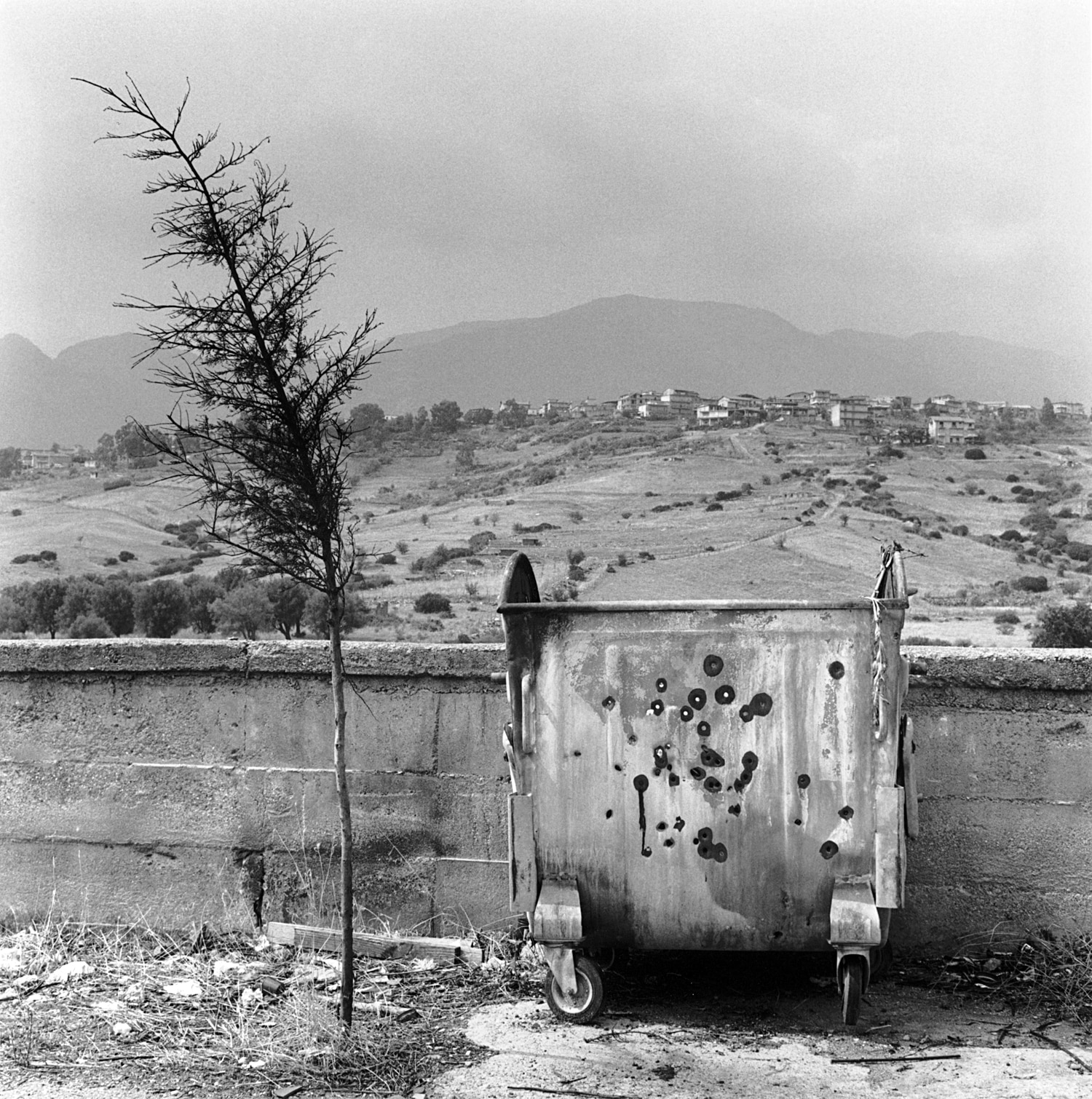 Garbage bin riddled with bullet holes in San Luca.