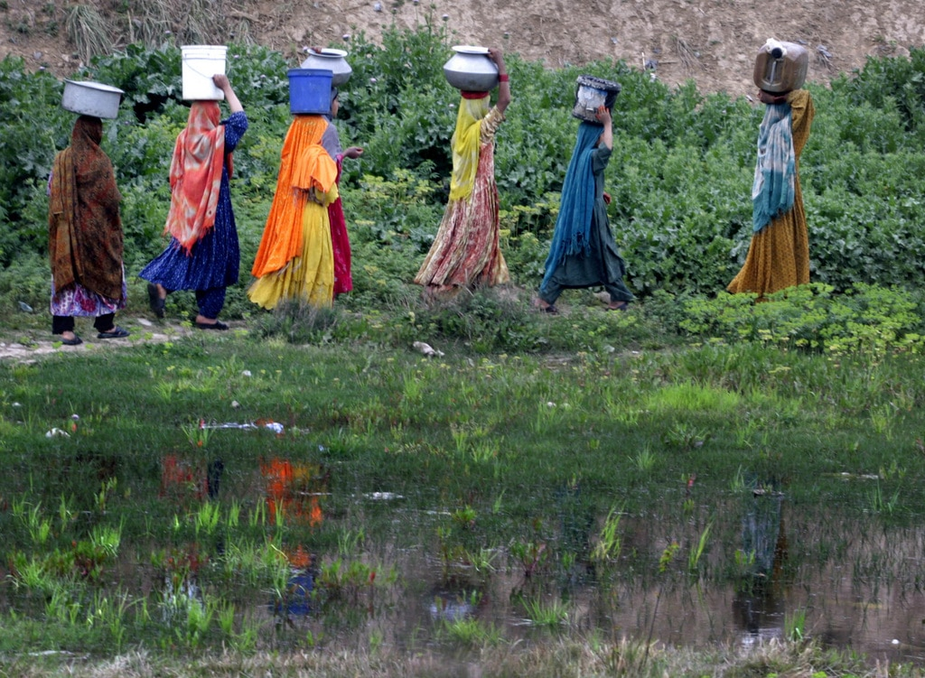 Women make their way home after collecting fresh water from a water point on the outskirts of Islamabad, Pakistan.