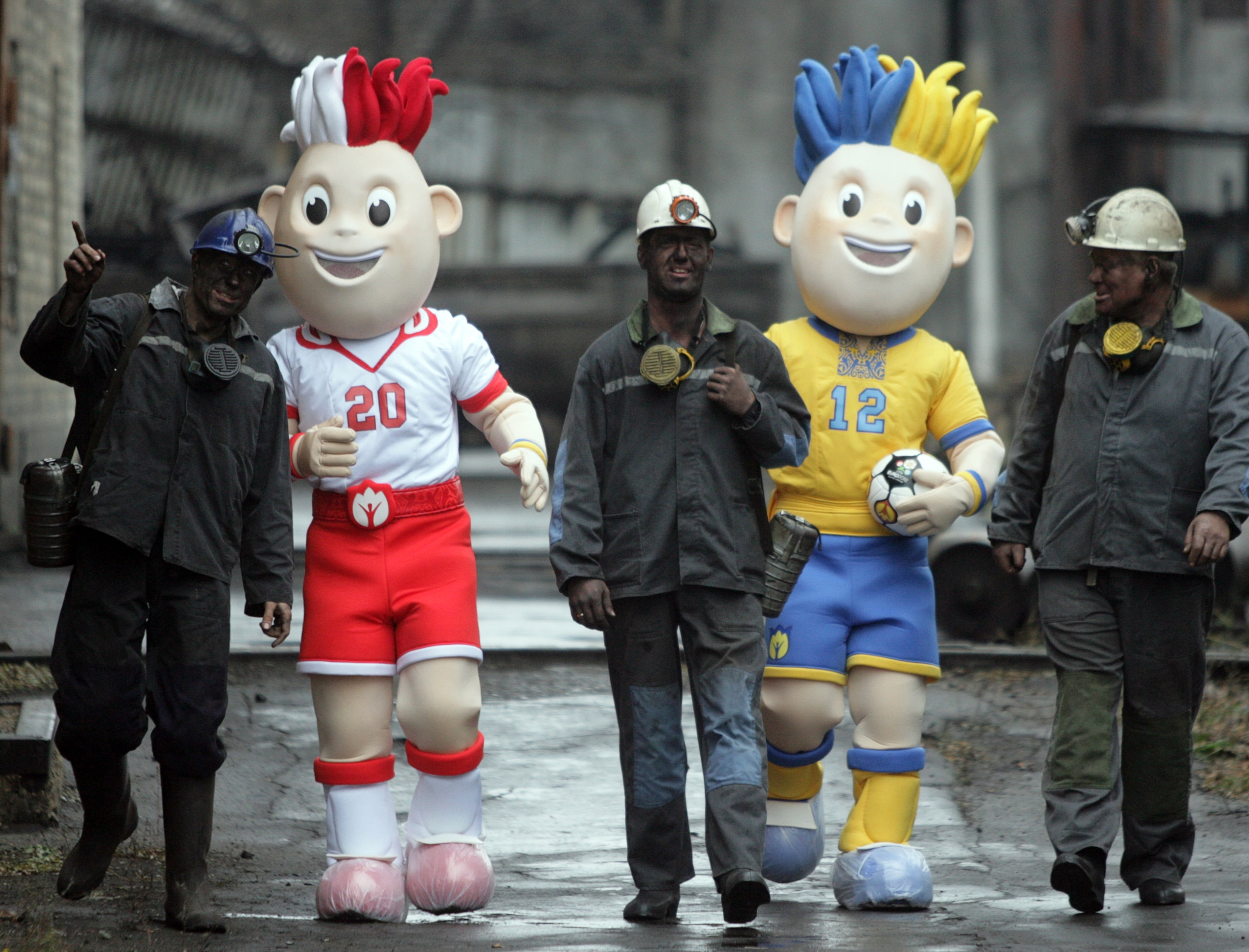 The Euro 2012 twin mascots - one wearing Ukraine's national blue and yellow colours, the other Poland's white and red - walk with miners in the Kalinin coal mine in the industrial Ukrainian city of Donetsk.