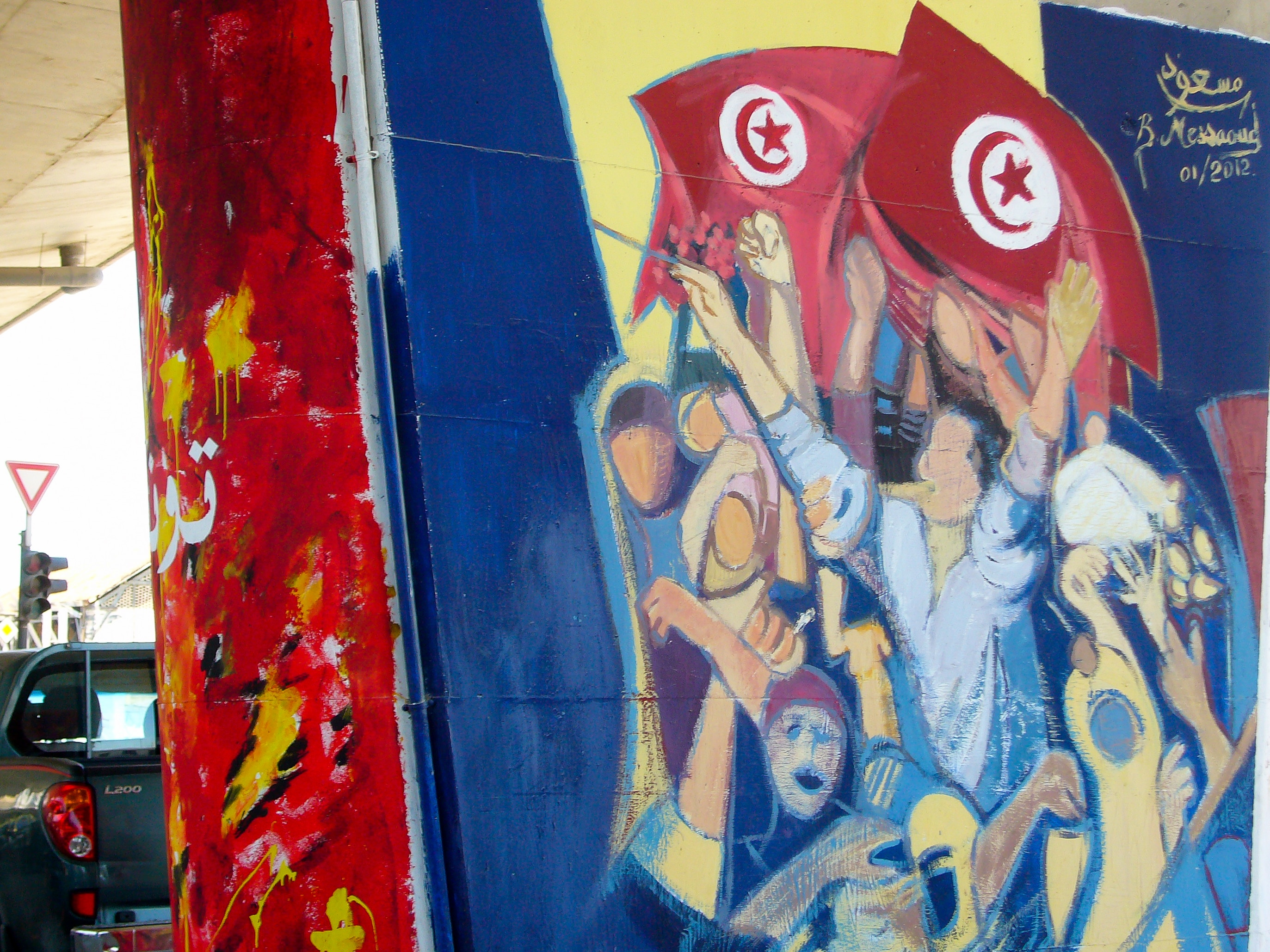 "Tunisian flags feature in many of the pictures. The raised hands again reflect the well-known gesture that accompanied the chanting of the slogan ""dégage""."