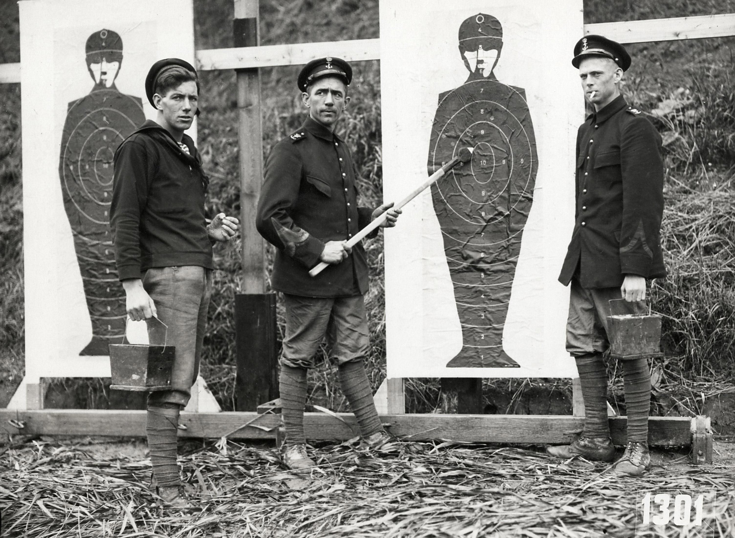 Juízes da prova de tiro, de uniforme e cigarro na boca, nos JO de Amsterdã, em 1928.