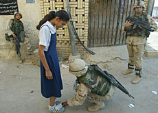 An Iraqi schoolgirl is searched by a soldier in Baghdad