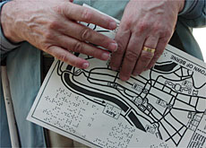 A blind tourist reads a relief map with brail descriptions