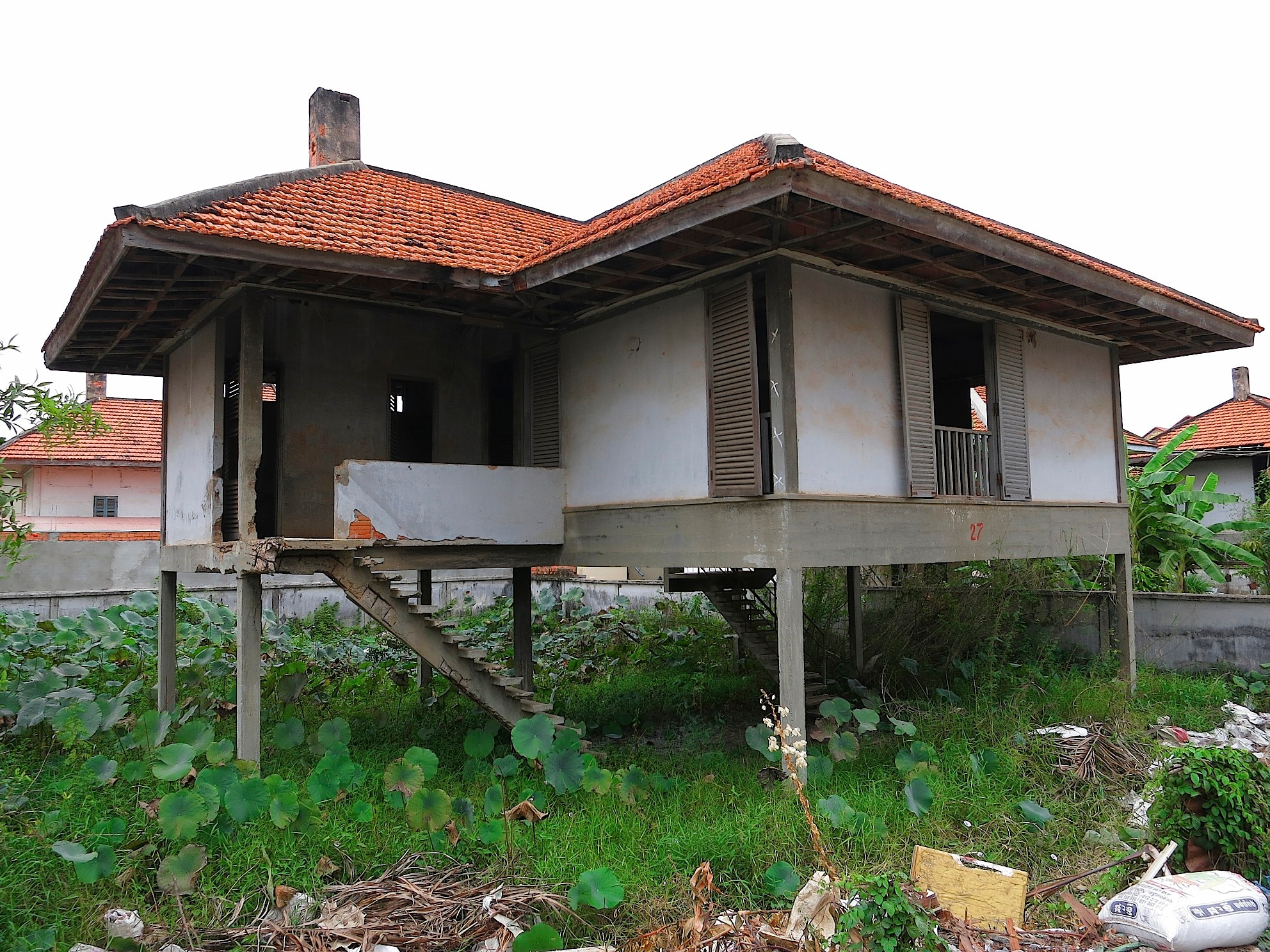 "This house, commissioned in 1965 by the National Bank of Cambodia to house its employees, is one of Molyvann's ""100 houses"" whose design was based on traditional Khmer homes. It eventually fell into a state of disrepair."