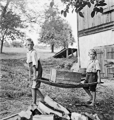 Two boys at a farm carrying a wooden box with a barrow