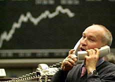 An unidentified trader works the phones at the German stock exchange in Frankfurt (AP)
