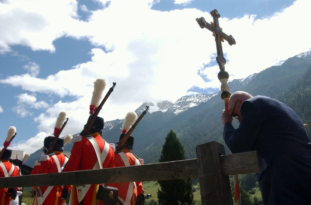 A man prays while grenadiers in historical costumes pass by during the Catholic Corpus Christi holiday procession in Kippel, canton Valais. (Keystone)