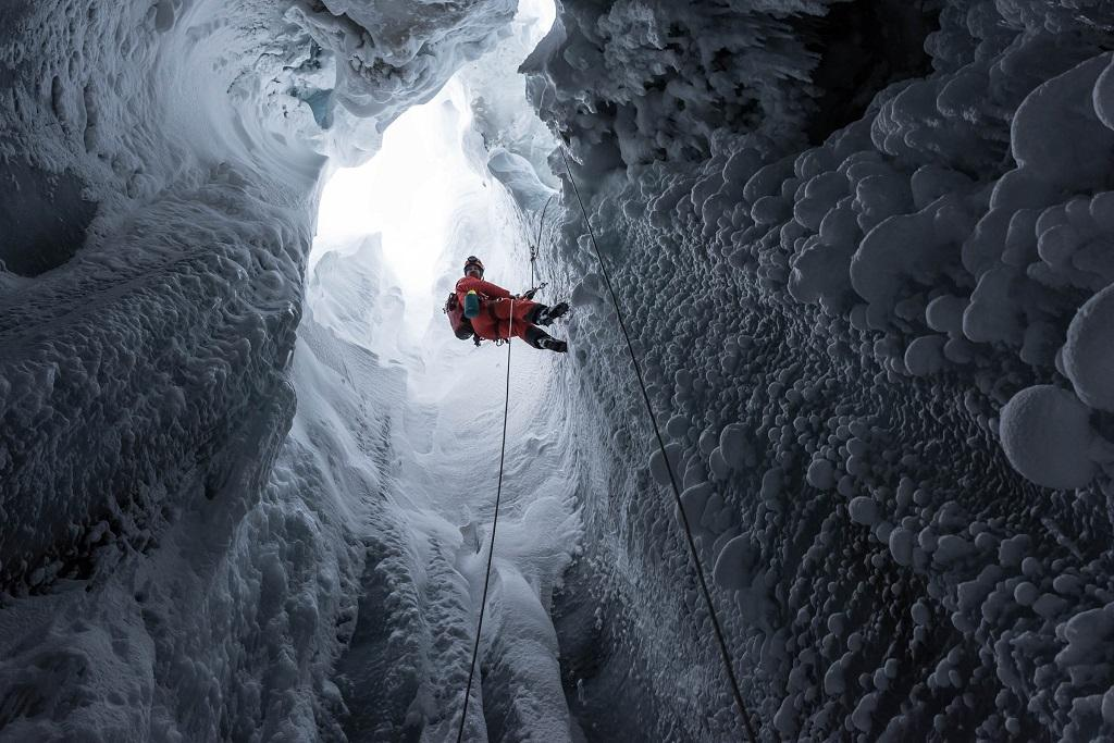 Man seen from below abseiling into deep hole in glacier