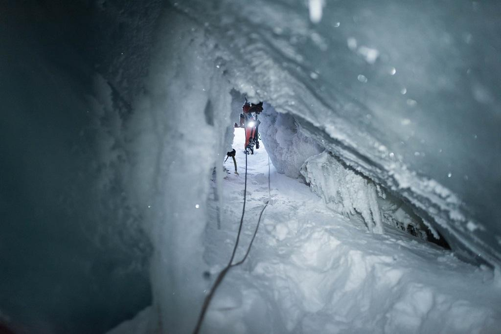 A small corridor in ice with men at end of opening shining a flashlight into it.