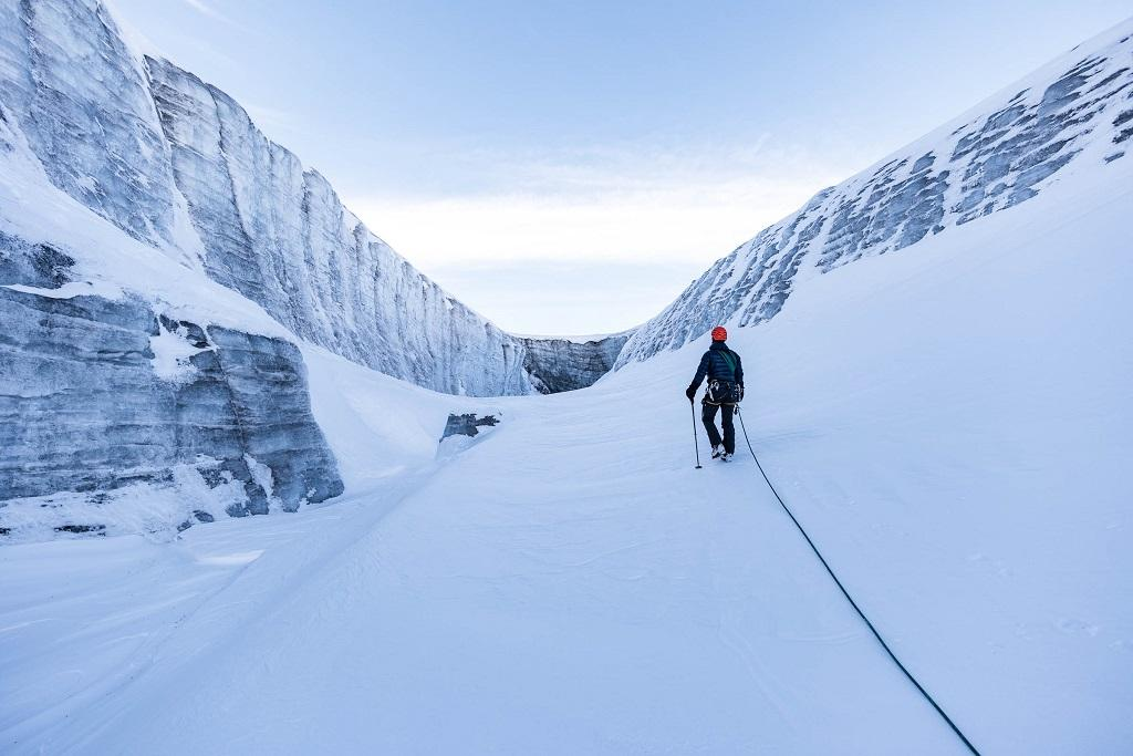 A man walks across the snow-covered channel of the glacier
