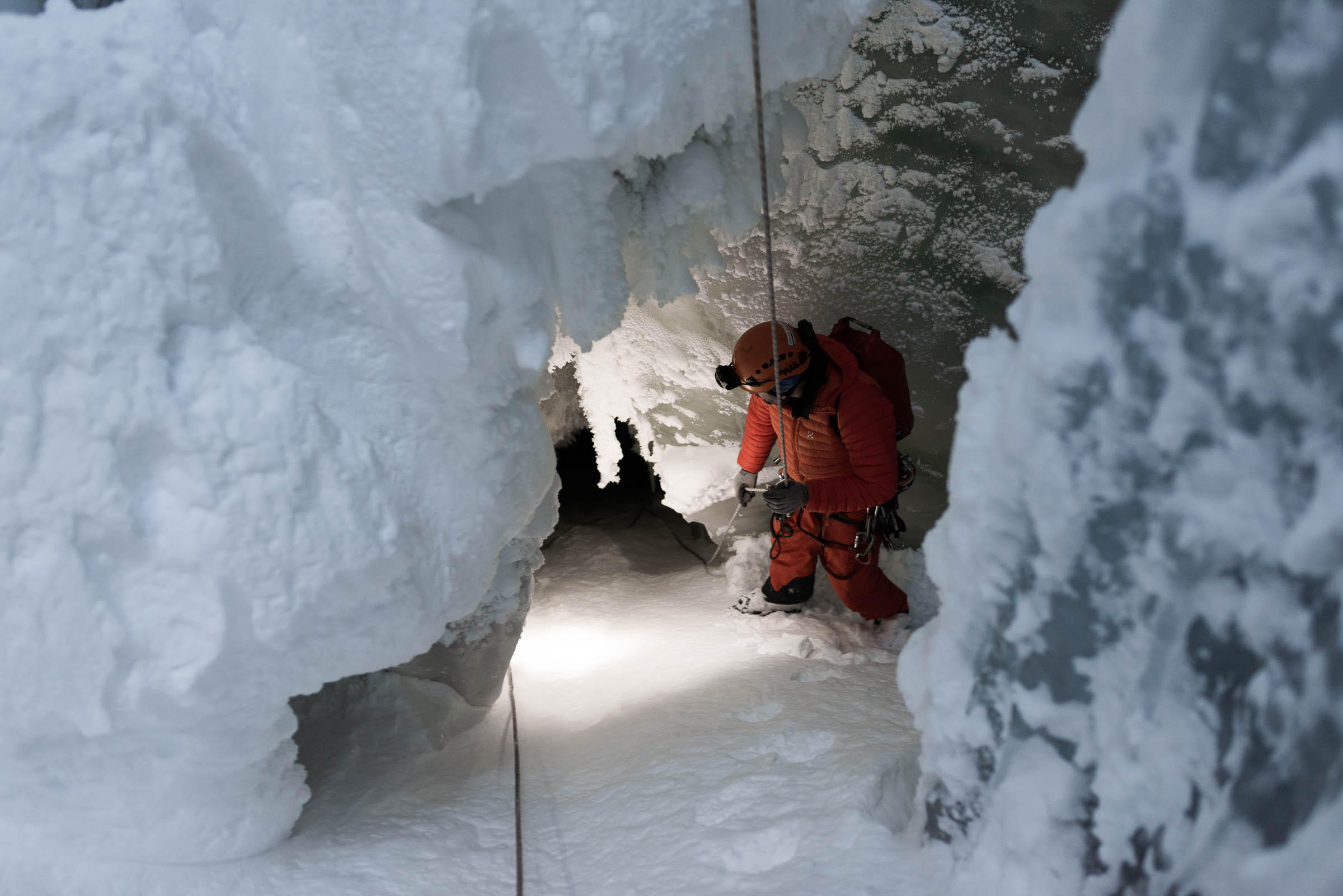 Man with headlamp peers into hole in glacier