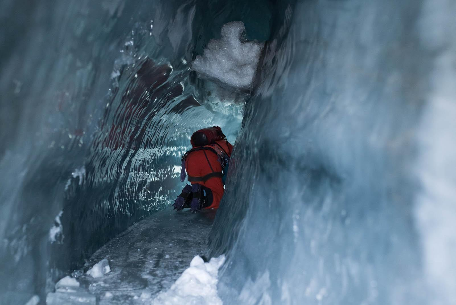 Man crawls through narrow icy tunnel on all fours