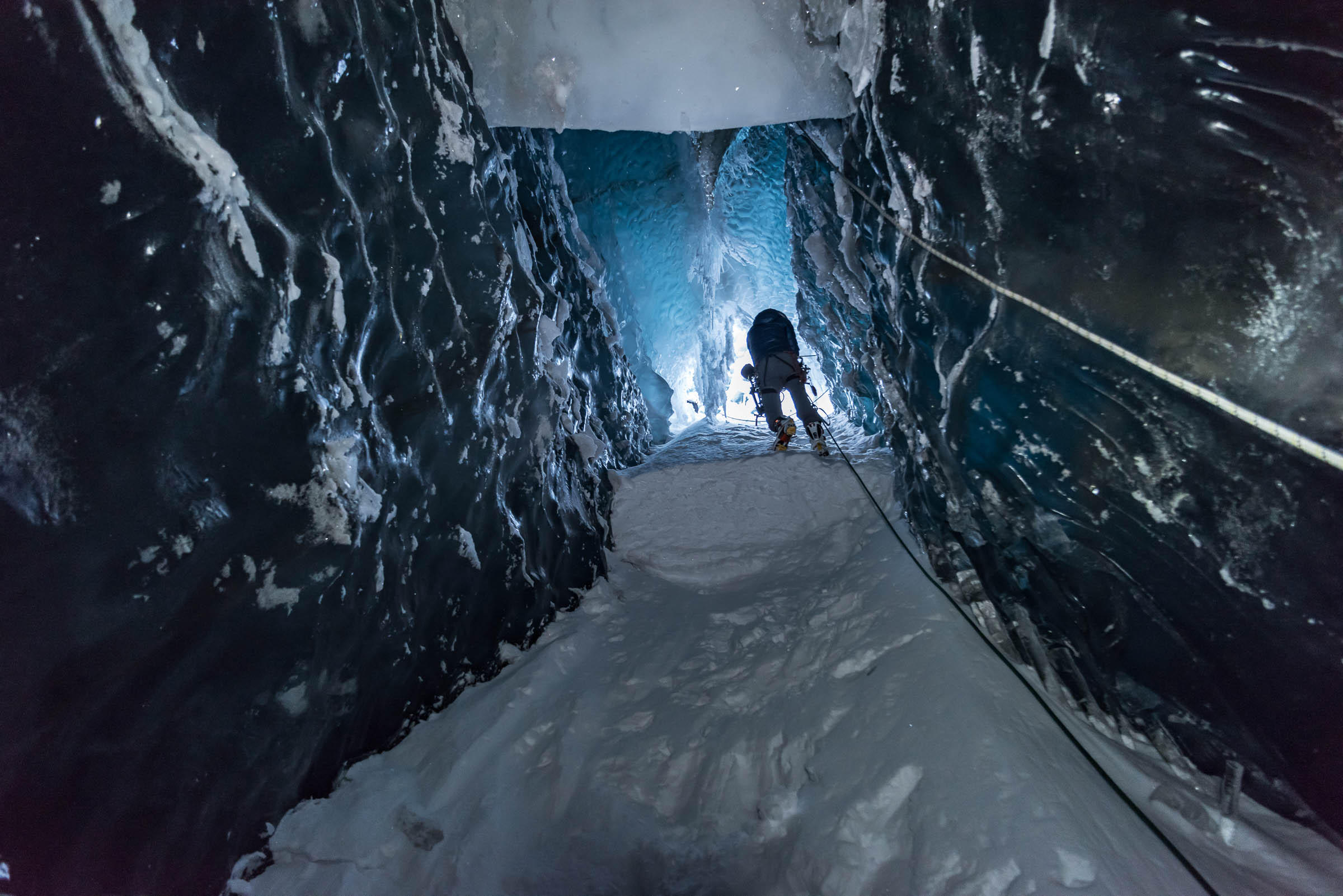 Man climbs up a shaft in the glacier, seen from below