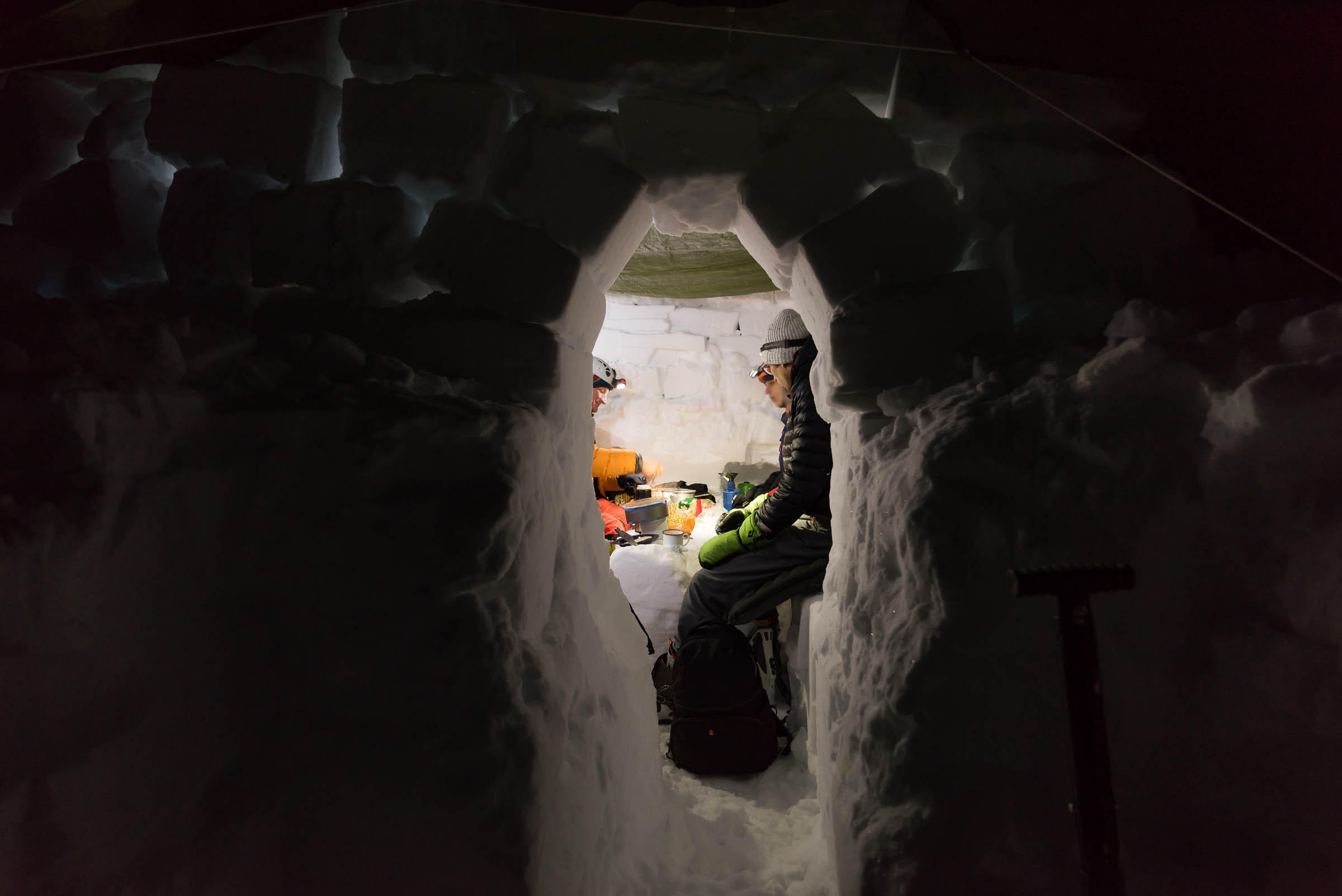 Men seen through hole in ice, sitting.