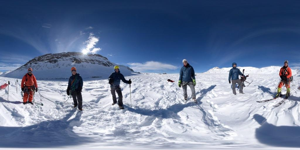 The four members of the team standing atop the glacier