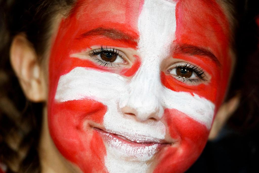 Una bambina con il volto dipinto come la bandiera rossocrociata della Svizzera