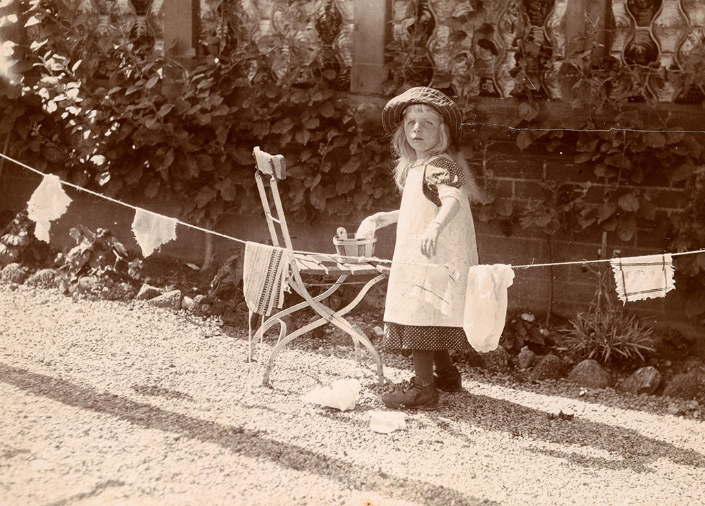 little girl stands next to washing line