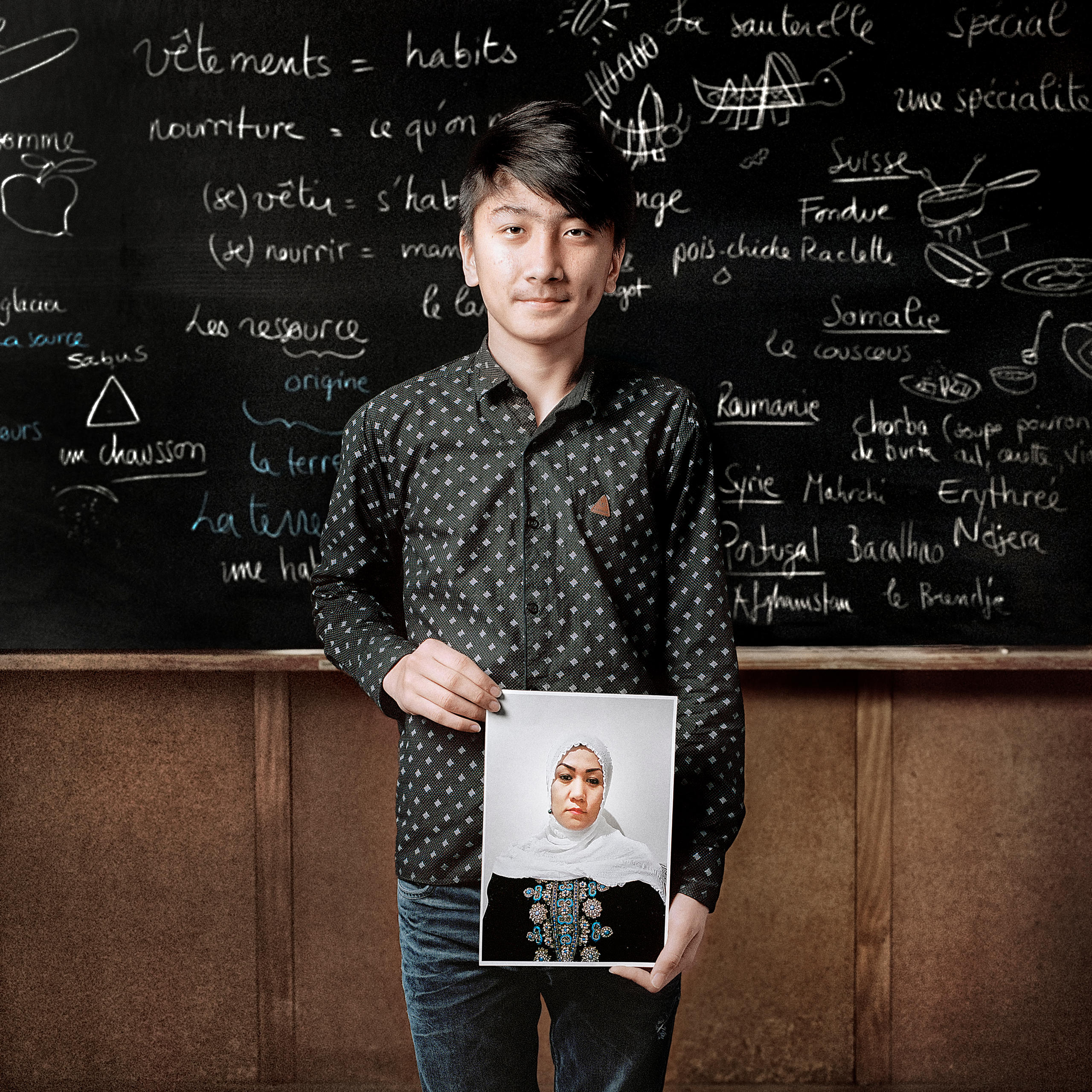 teenager stands in front of blackboard holding a photo