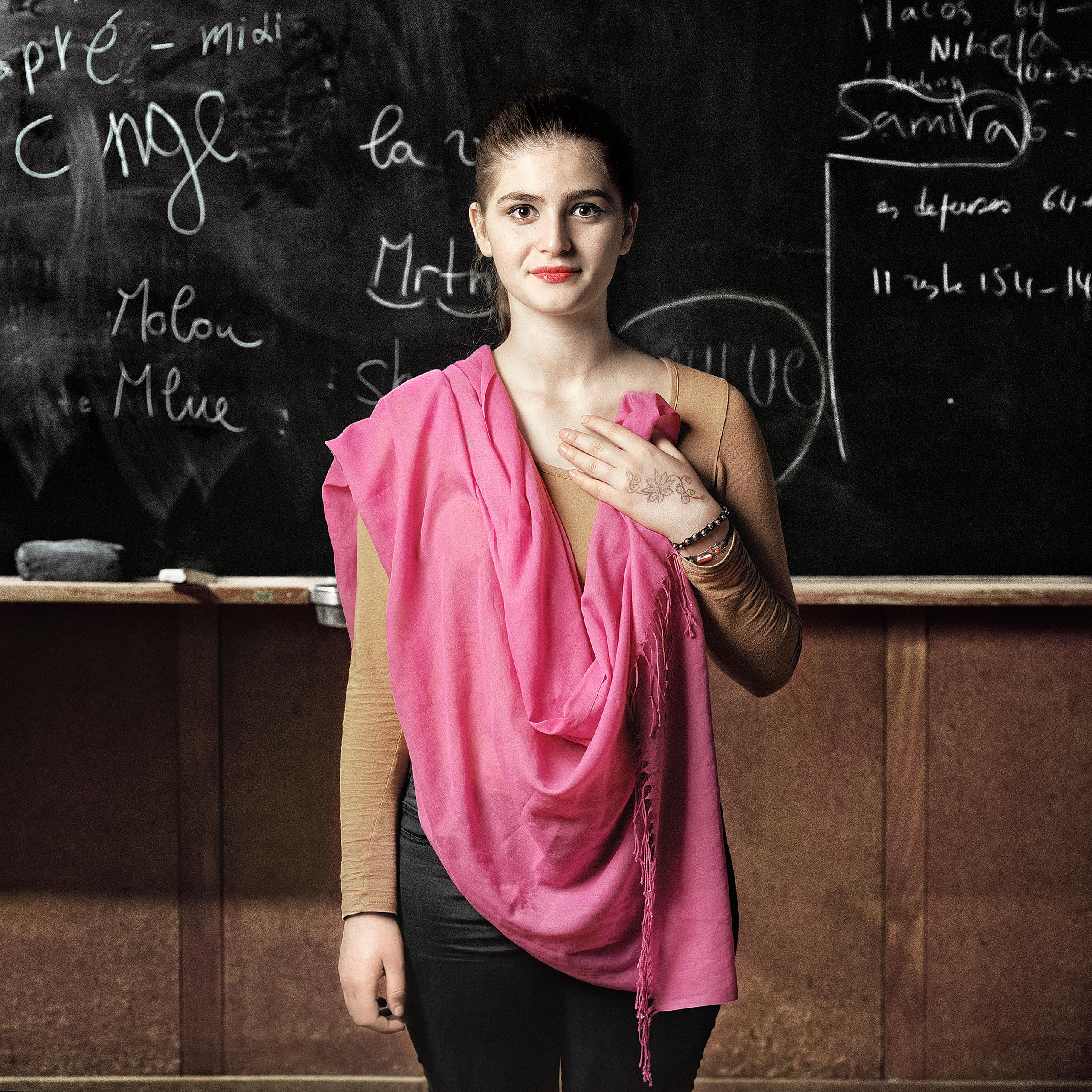 teenager stands in front of blackboard holding a pink shawl