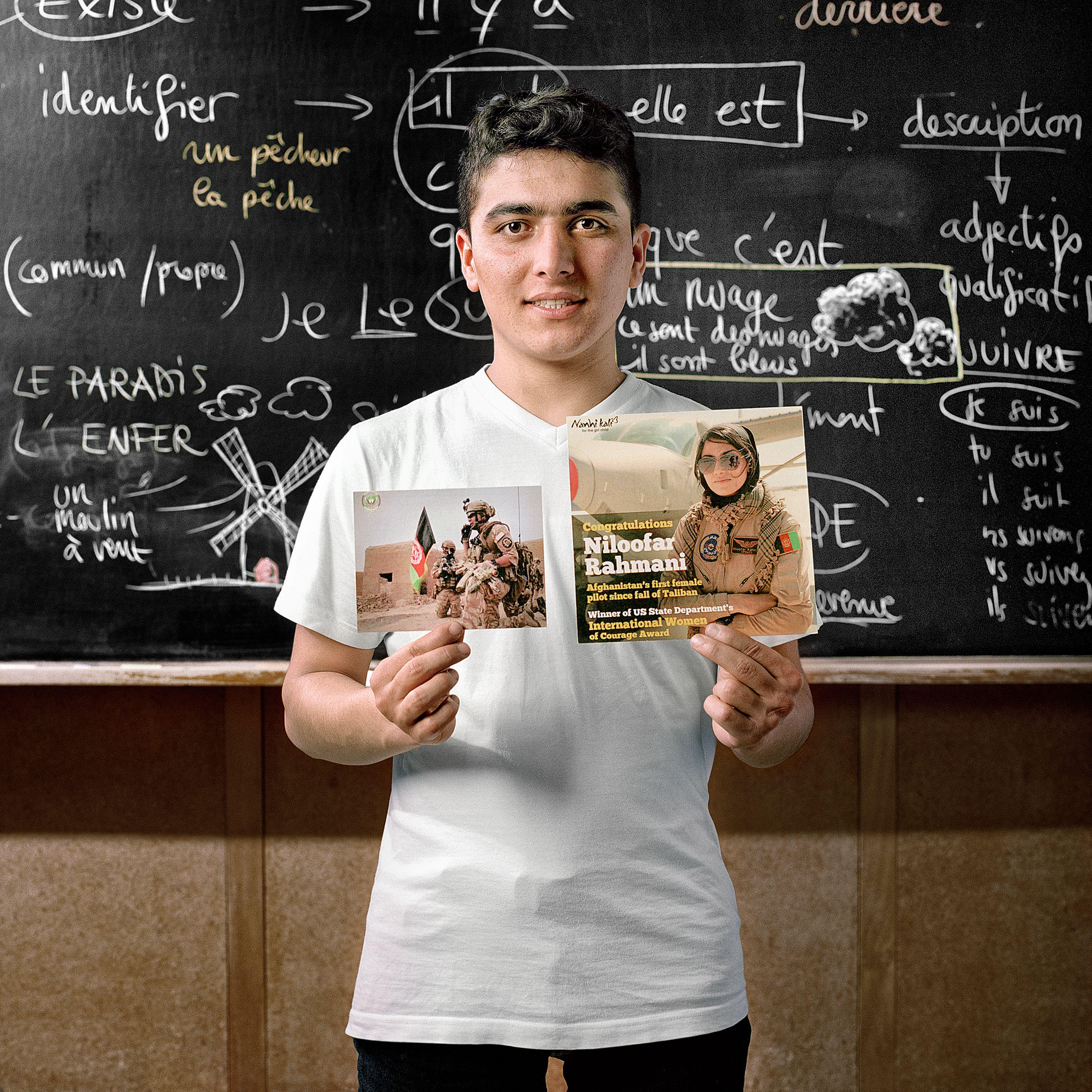 teenager stands in front of balckboard holding two photos