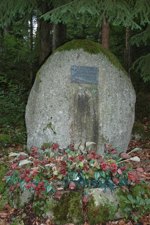 Grosse pierre avec une plaque en forêt.