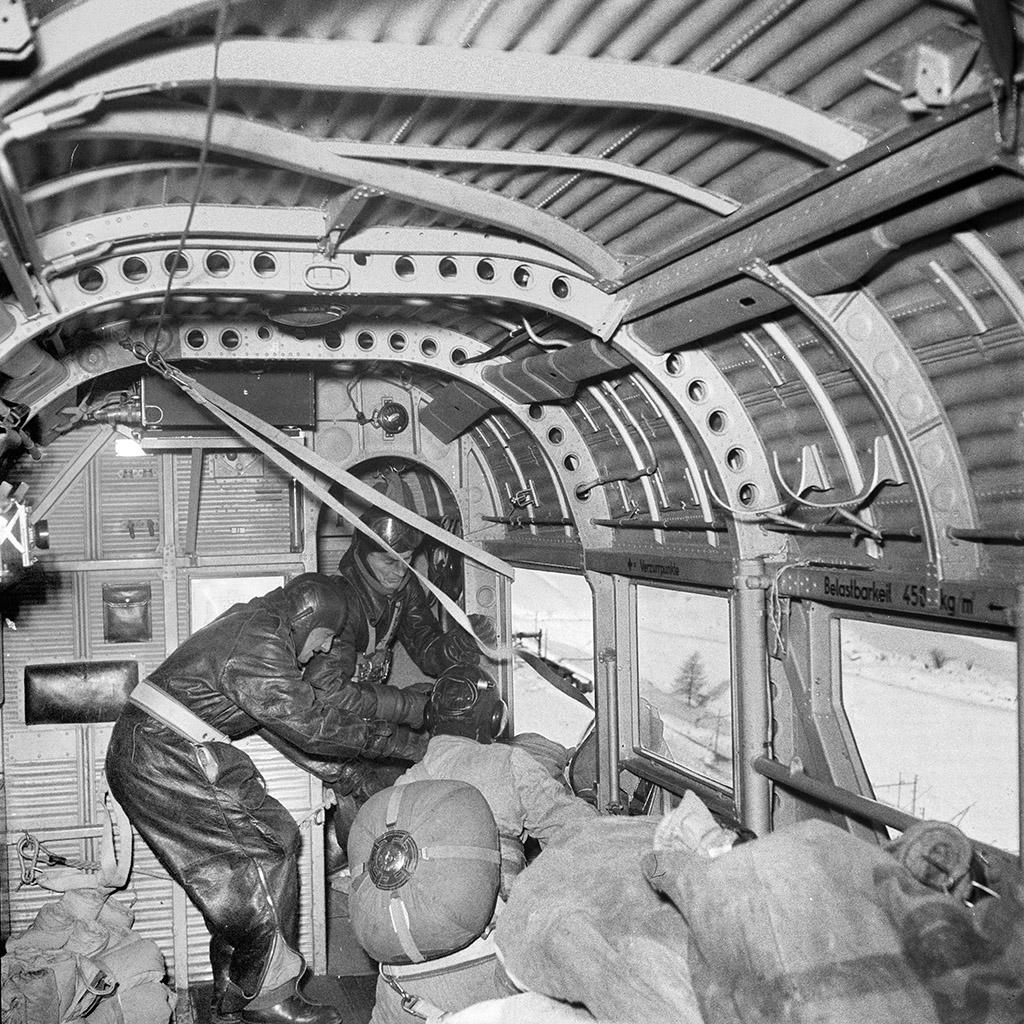 Two men throw parcels out of an airborne plane.