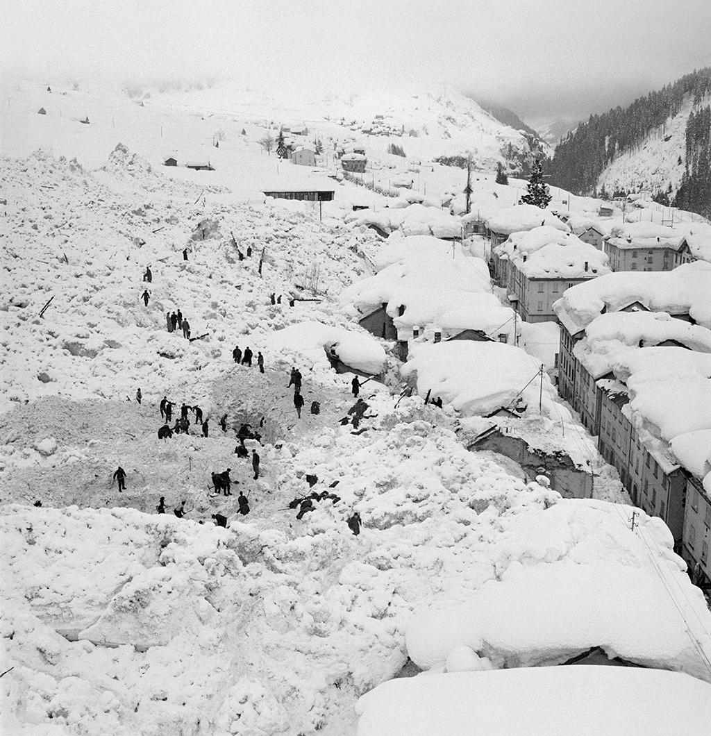 Many people walk through the scene of an avalanche scene of buried houses.