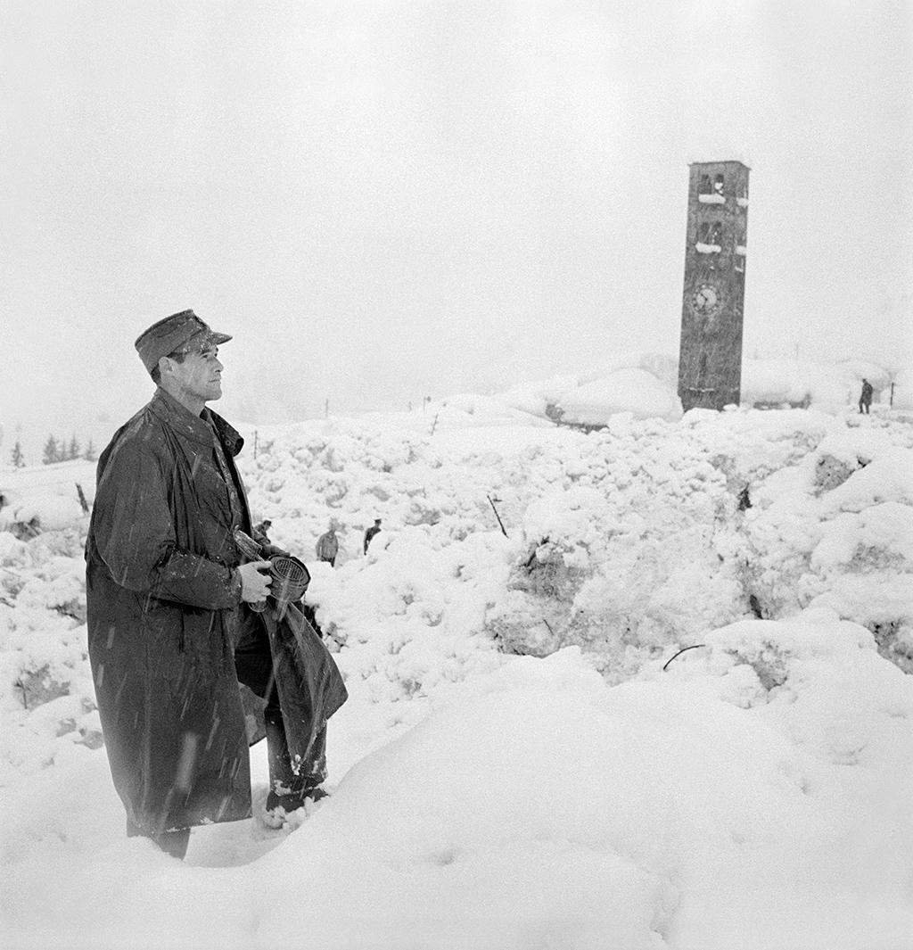 A man in uniform walks through the scene of an avalanche scene - a church tower is to been seen in the background