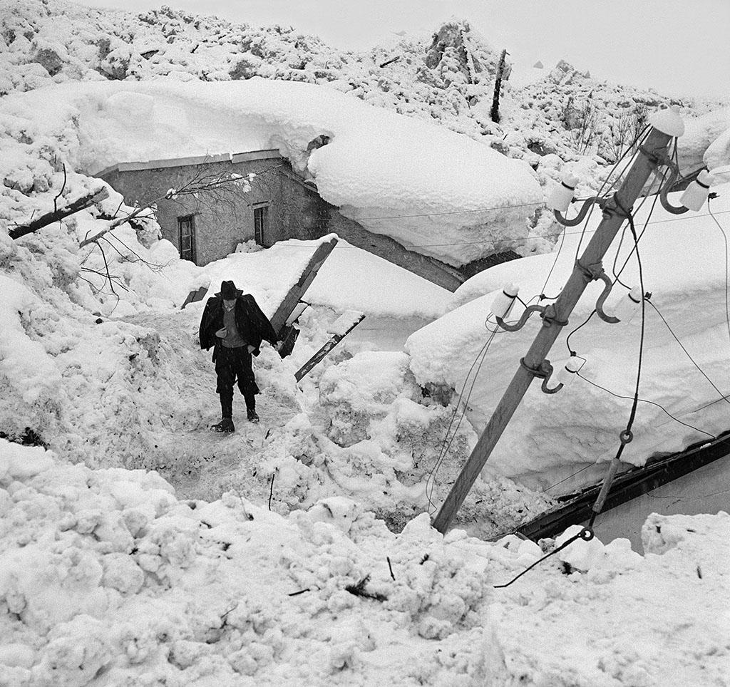 A man walks through the scene of an avalanche scene of buried houses.