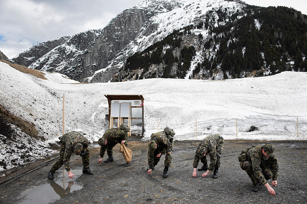 Army personnel pick up shot from a shooting range.