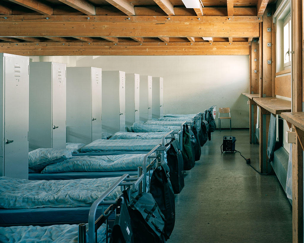 A row of unmade beds in a barrack